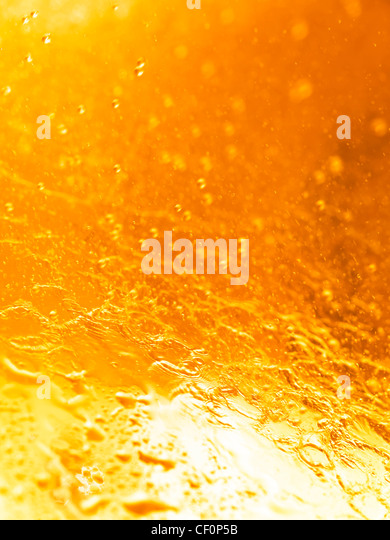 Closeup of splashing water abstract orange background texture - Stock Image