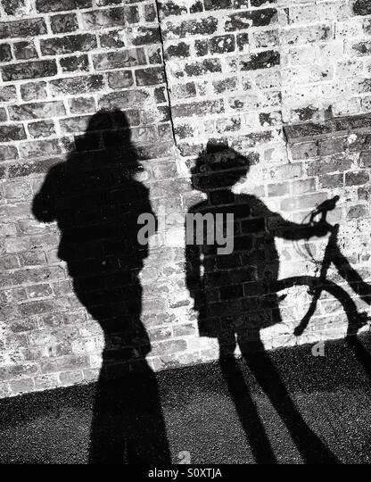 Shadow of girl, woman and bike - Stock Image