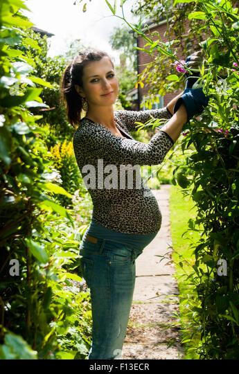 Smiling pregnant woman gardening - Stock Image