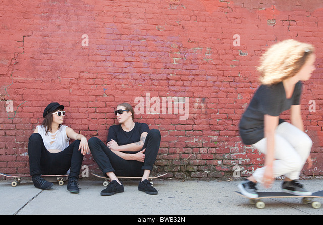 Skaters sitting on boards as other skater goes past - Stock-Bilder