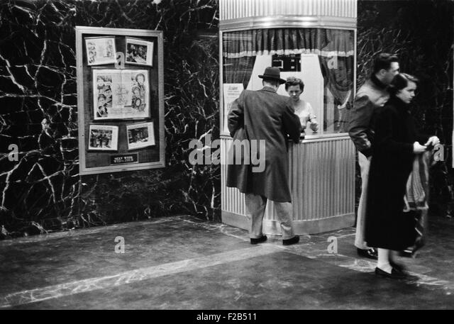 Man purchasing a movie ticket for the film. The coming attraction is the film, ALL MINE TO GIVE. Feb. 9, 1958.  - Stock Image