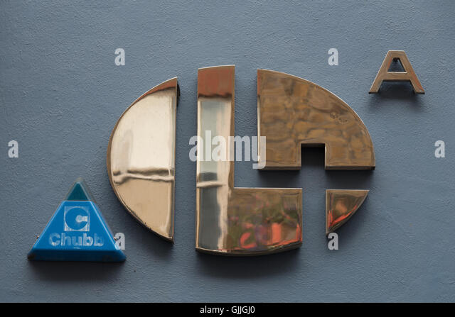 Minimalistic shiny brass Number 14 A door number and a blue Chubb intruder alarm that mirrors the shape of the A - Stock Image