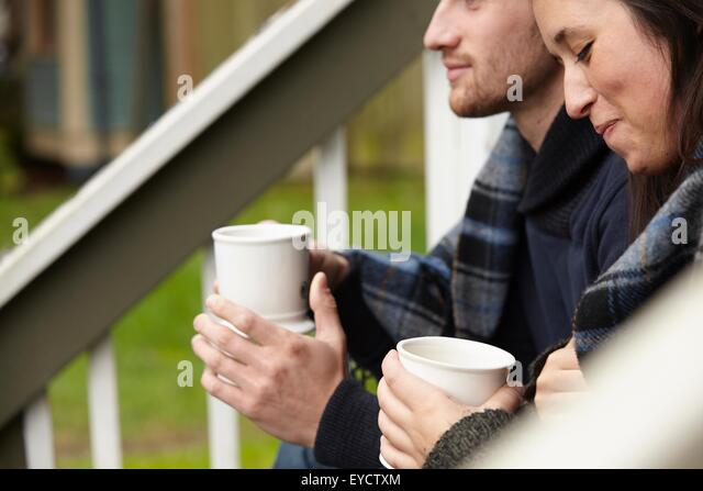 Cropped shot of young couple sitting on porch step drinking coffee - Stock Image