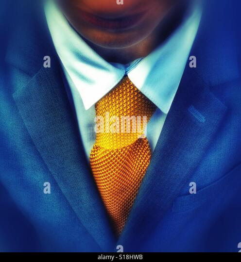 A boy wearing a suit with a bright yellow tie - Stock Image