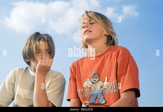 Two Boys sitting next to Each Other under the blue Sky - Friendship - Boredom - Youth - Stock Image