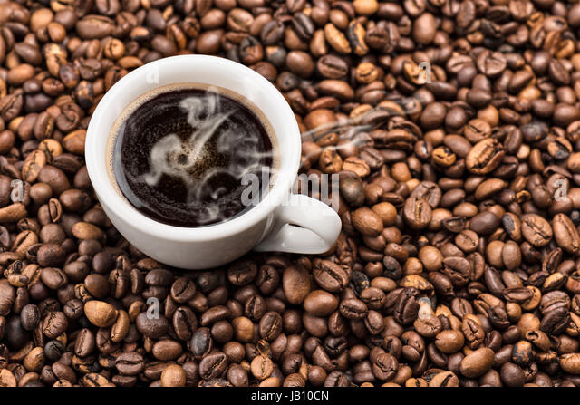 cup of steaming coffee on bunch of roasted coffee beans - Stock Image
