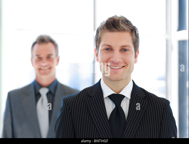 Senior and Junior business looking at the camera - Stock Image