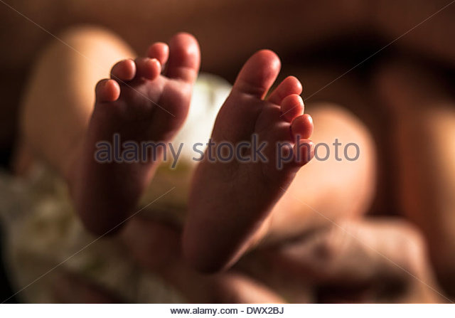 Selective focus on baby girl's feet - Stock Image