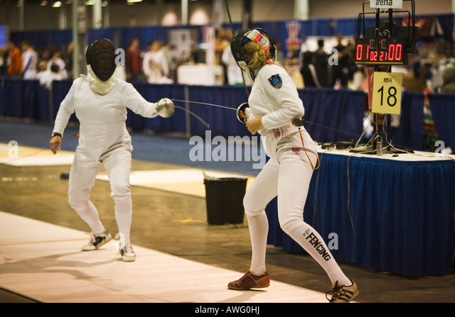 SPORTS Fencing competition epee weapon women in bout on strip lunging toward opponent scoreboard on table - Stock Image