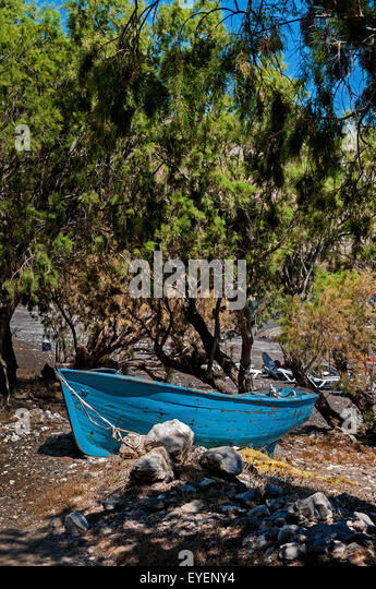 A beached rowing boat left on Eristos beach, Tilos. - Stock Image