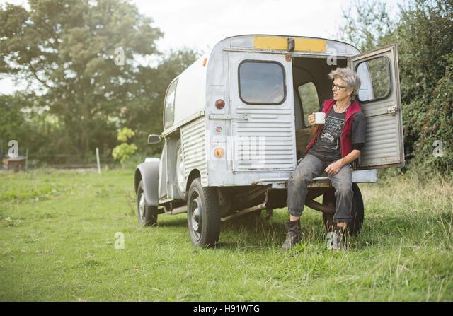 Elderly car mechanic having a tea break - Stock Image