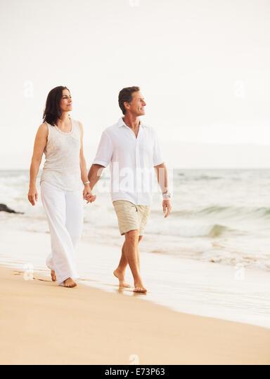 Mature Retired Couple Enjoying Sunset Walk on the Beach - Stock Image