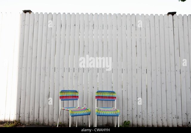 Two chairs by fence - Stock Image