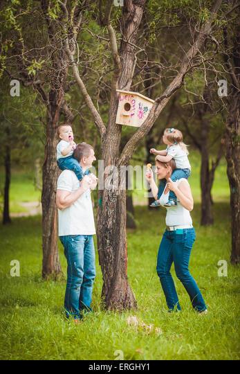 Happy family with Wooden birdhouse - Stock-Bilder