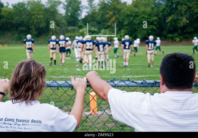 Two spectators watch amateur American Football in Clayton, Alexandria Bay, Upper New York State - Stock Image