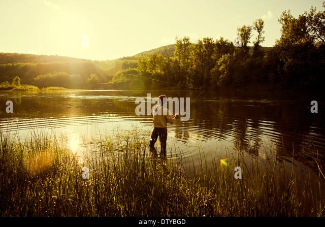 Caucasian man fishing in still lake - Stock Image