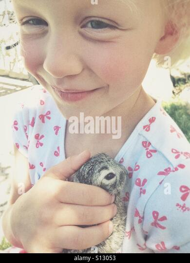 A young girl proudly protects the wild baby rabbit she rescued from a bird attack. - Stock Image