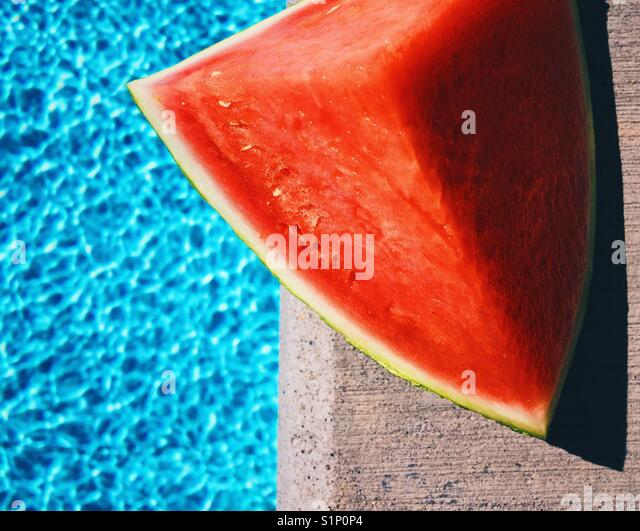 A wedge of sweet read watermelon sitting at the edge of a swimming pool outdoors on a sunny summer day. - Stock Image