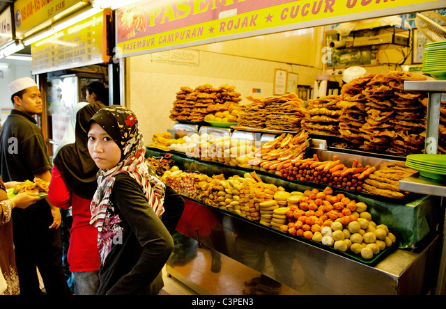 veiled muslim girl at snack stand in penang malaysia - Stock Image
