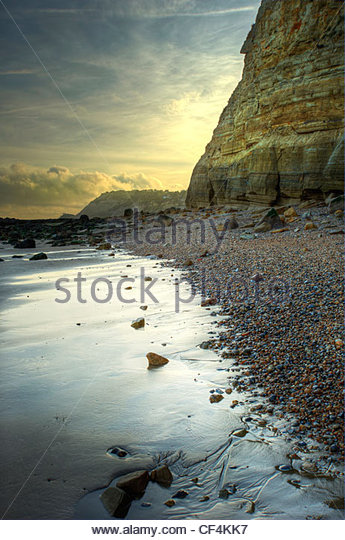 Fairlight beach at dawn with the sun coming over horizon. - Stock Image