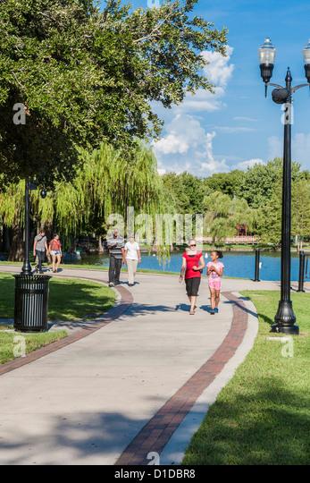 Multi-cultural people walking through Lake Eola Park in downtown Orlando, Florida - Stock Image