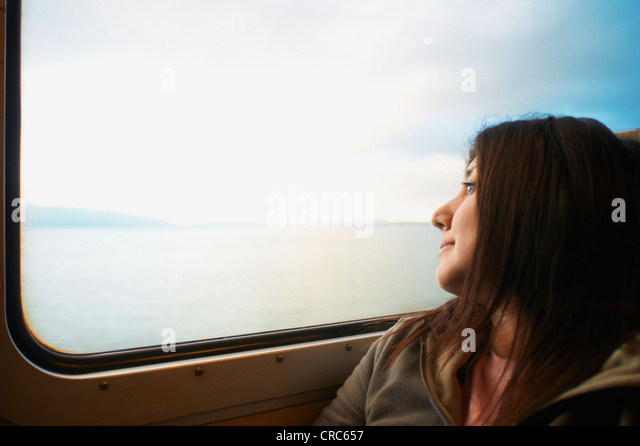 Woman looking out train window - Stock Image