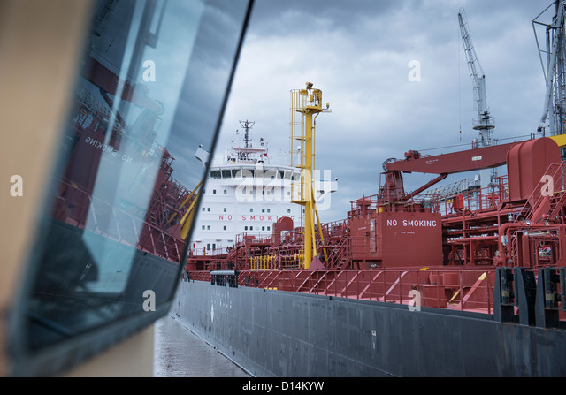Tugboat overlooking stern of ship - Stock Image