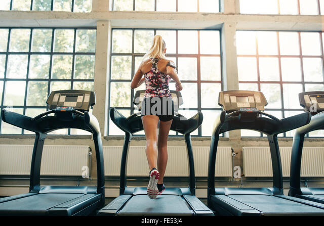 Horizontal shot of woman jogging on treadmill at health club. Female working out at a gym running on a treadmill. - Stock-Bilder