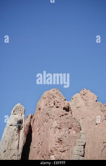 USA, Colorado, El Paso, Colorado Springs, Garden of the Gods, Garden Drive, Rock climber climbing spire - Stock Image