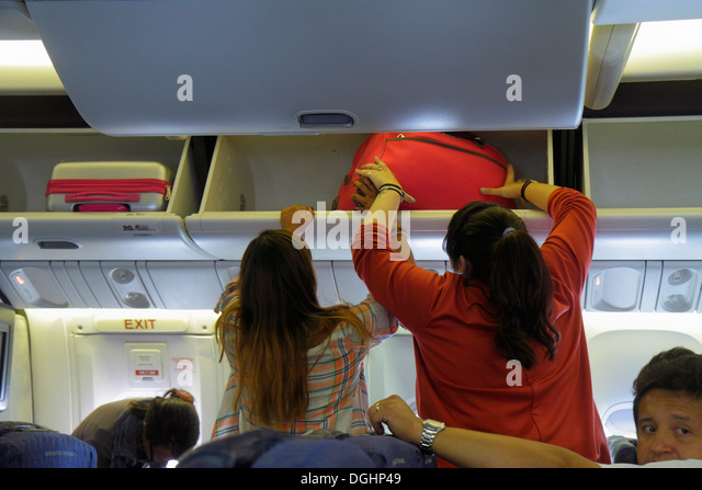 Paris France Europe French CDG Charles de Gaulle Airport American Airlines onboard cabin overhead luggage bin storage - Stock Image