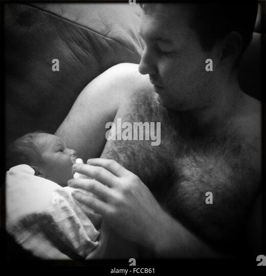 Father Holding Newborn Baby In Arms - Stock Image