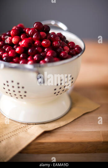 Bright red cranberries in a cream colored strainer. Sitting on a mustard linen on butcher block. - Stock Image