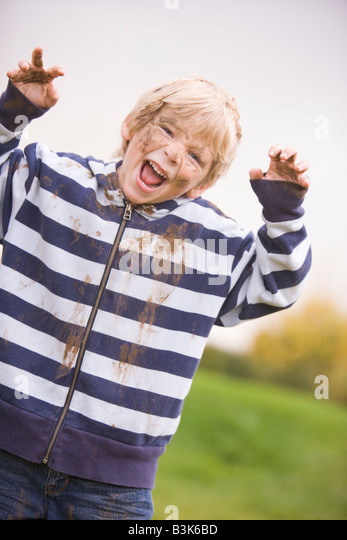 Young boy standing outdoors dirty and smiling - Stock Image