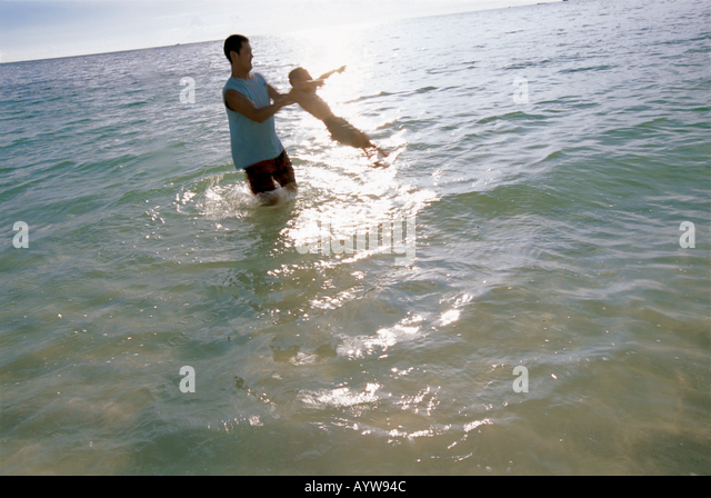 Father holding his son in the air in the ocean - Stock-Bilder