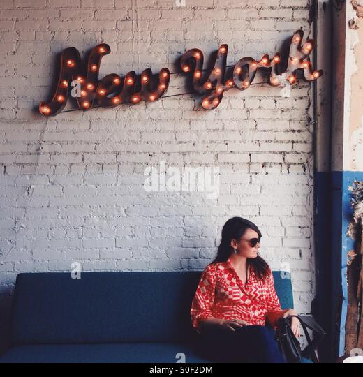 New York Wall Sign and Woman Sitting - Stock Image