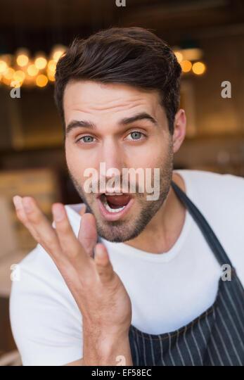Handsome waiter making tasty gesture - Stock Image