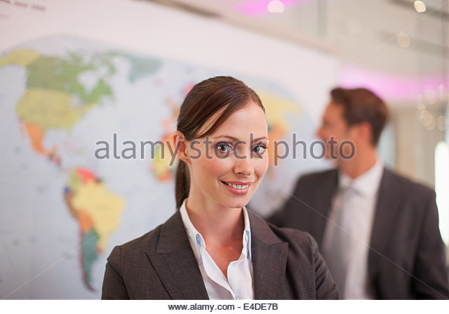 Business people standing by world map - Stock Image