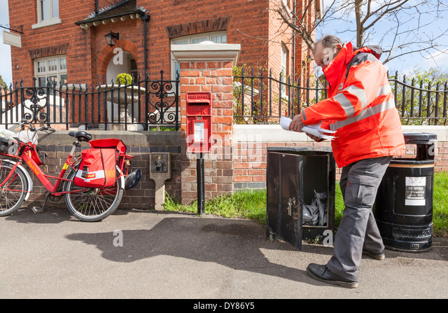 Postman collecting and checking mail from a box outside the Old Post Office Plumtree, Nottinghamshire, England, - Stock Image