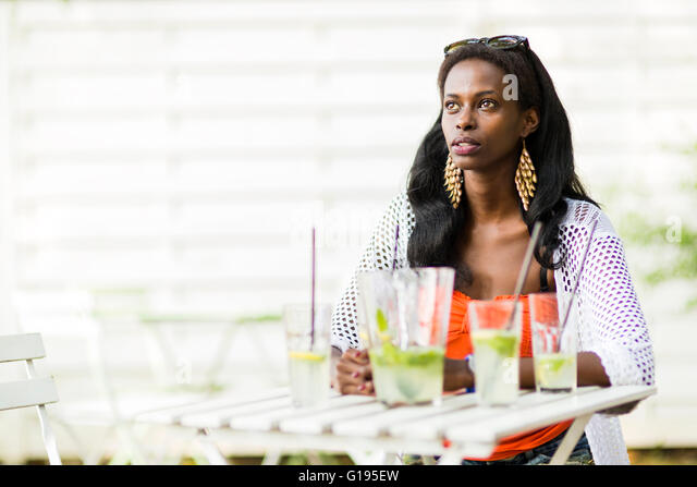 Beautiful woman is sitting at a table alone and waiting for friends - Stock Image