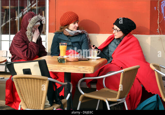 Young women dressed in woolly hats and blankets enjoy hesitant sunshine and temperatures around 10 degrees centigrade - Stock Image