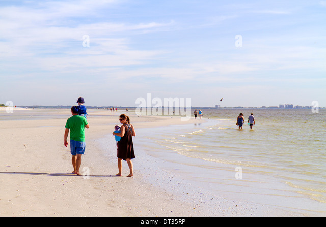 Sanibel Island Florida Gulf of Mexico beach beachcombers family man father woman mother children - Stock Image
