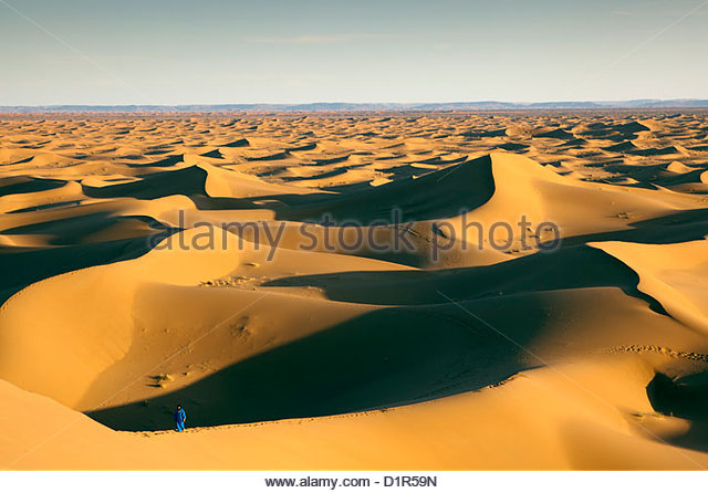 Morocco, M'Hamid, Erg Chigaga sand dunes. Sahara desert. Local Berber man on sand dune, background tourist camp, - Stock Image