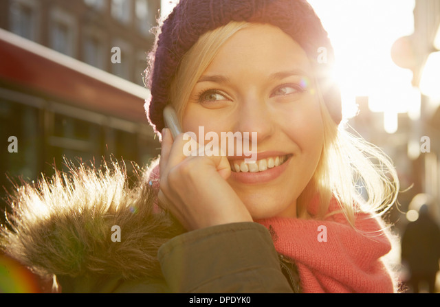 Portrait of young woman wearing knit hat, telephone call - Stock Image