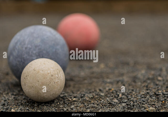 Close Up of Three Bocce Balls With White In Focus on gravel - Stock Image