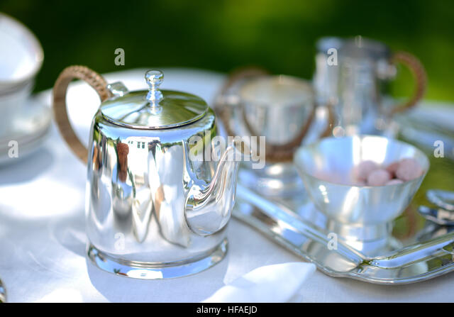 Table set for an English high tea, or afternoon tea, outside with silver teapot and linen tablecloth - Stock Image