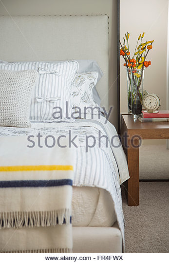 Close-up of modern bedroom with flowers on bedside table. - Stock Image