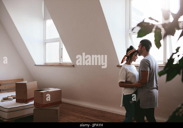 Indoor shot of loving young couple moving into their new home. Man and woman in love standing together with cardboard - Stock Image