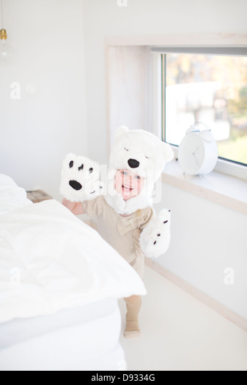 Girl wearing polar bear costume hiding behind bed - Stock Image