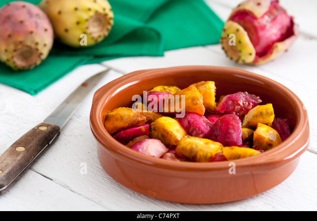 Sliced Indian Figs in a Bowl on White Wood - Stock Image