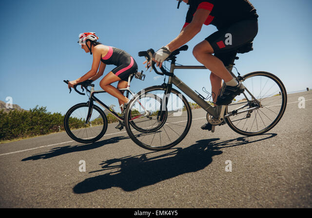Action shot of a racing cyclists. Cyclist riding bicycles down hill on country road. Practicing for competition. - Stock Image